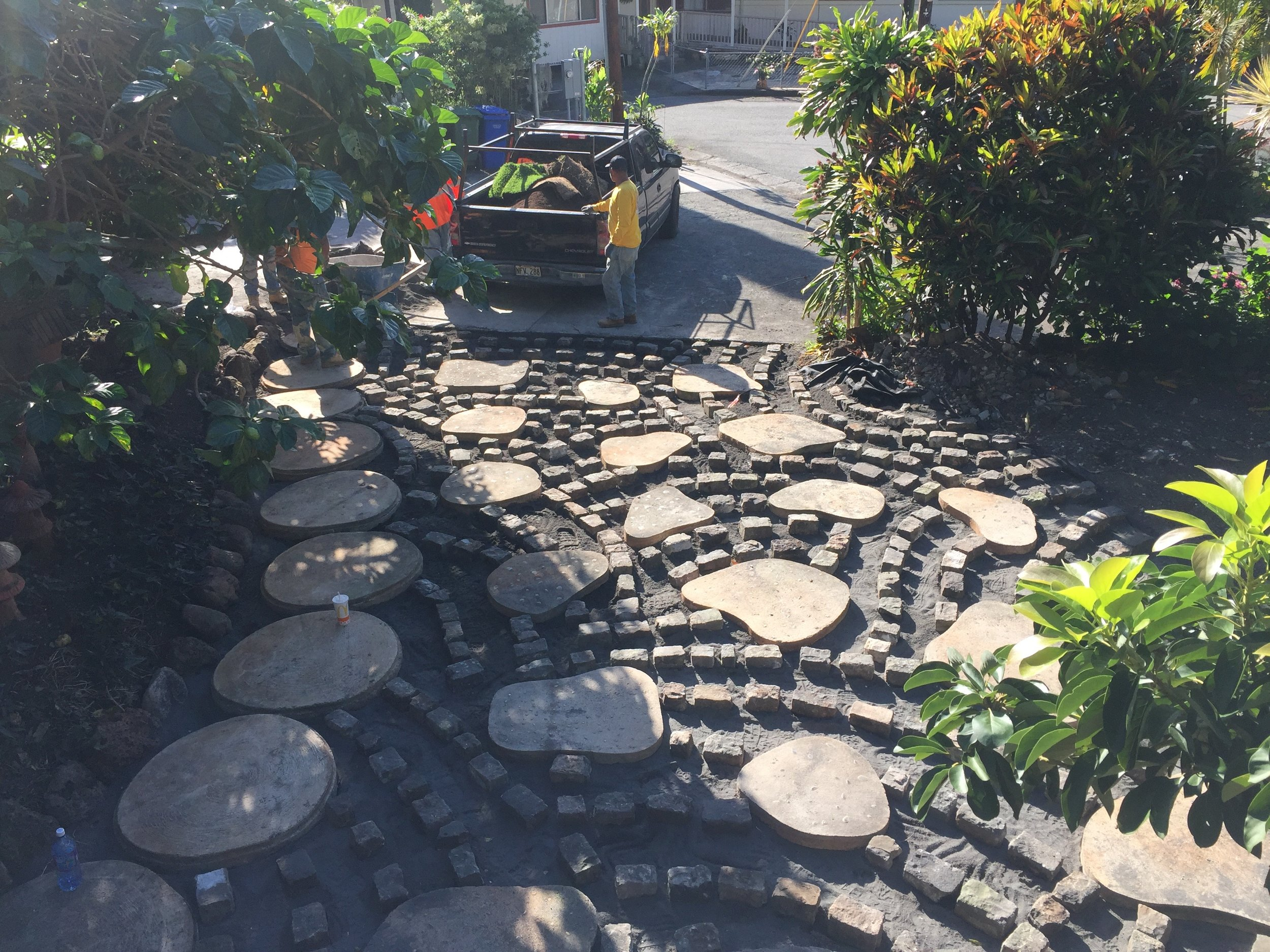 Above: Reclaimed cobblestones salvaged from old Iwalei Rd. are arranged in a fish scale pattern.