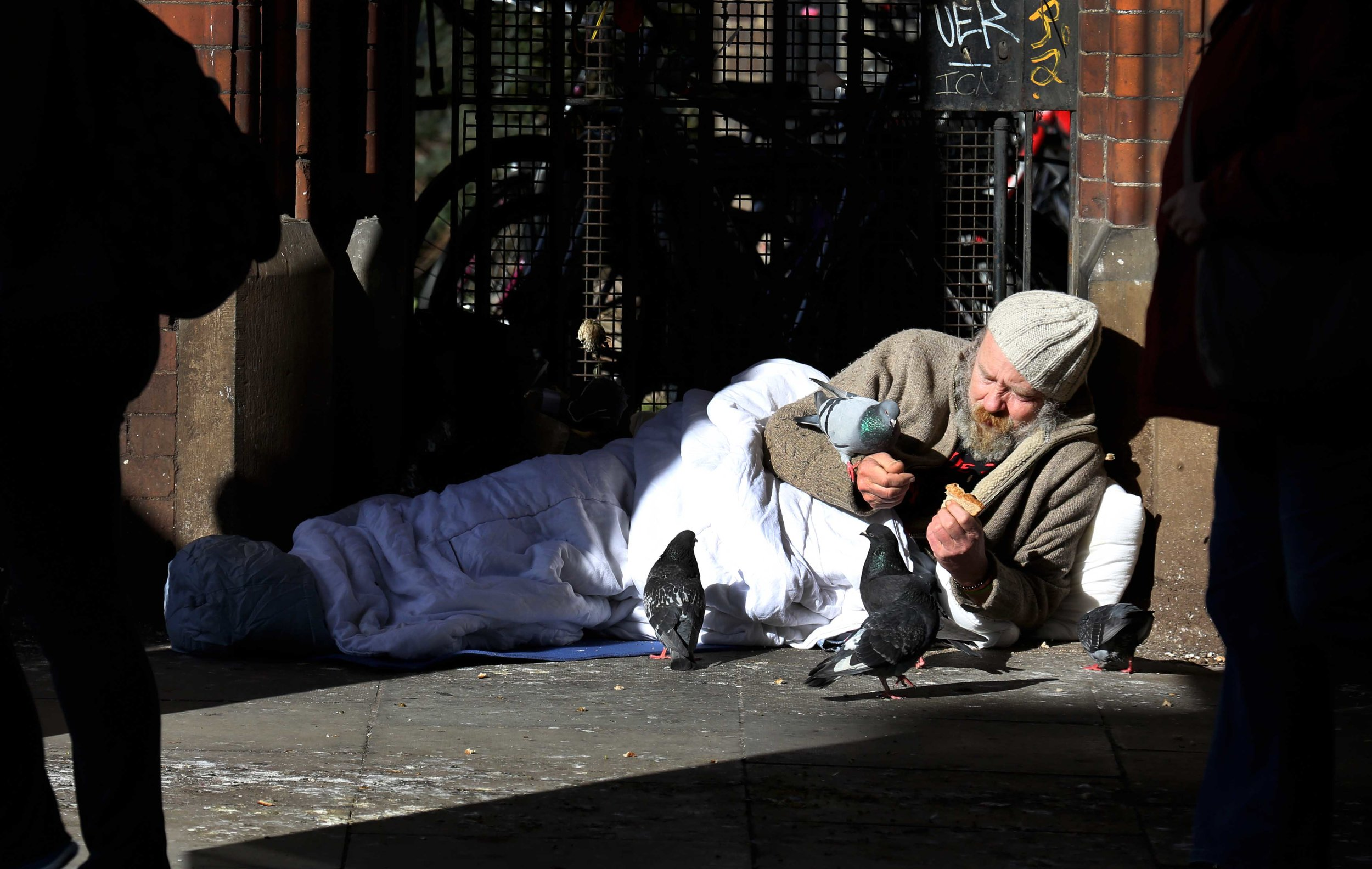 Martin Hart feeds pigeons from his sleeping bag on Westland Row