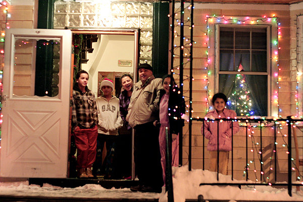 A family braves the cold to receive a song from carolers (2009)  Photo Credit: Elaine Collins