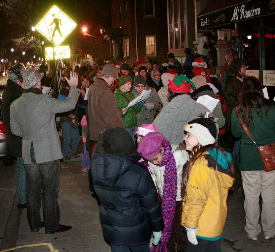 Conductor Glenn Zienowicz leads carolers down Westminster Street (2013)  Photo Credit: Elaine Collins