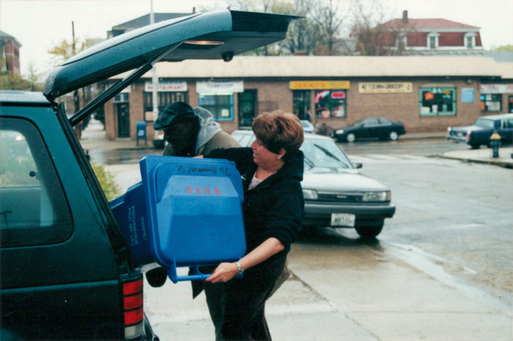 Neighbor-organizer Karen Ziner helps a neighbor on Hammond Street load up (2000)