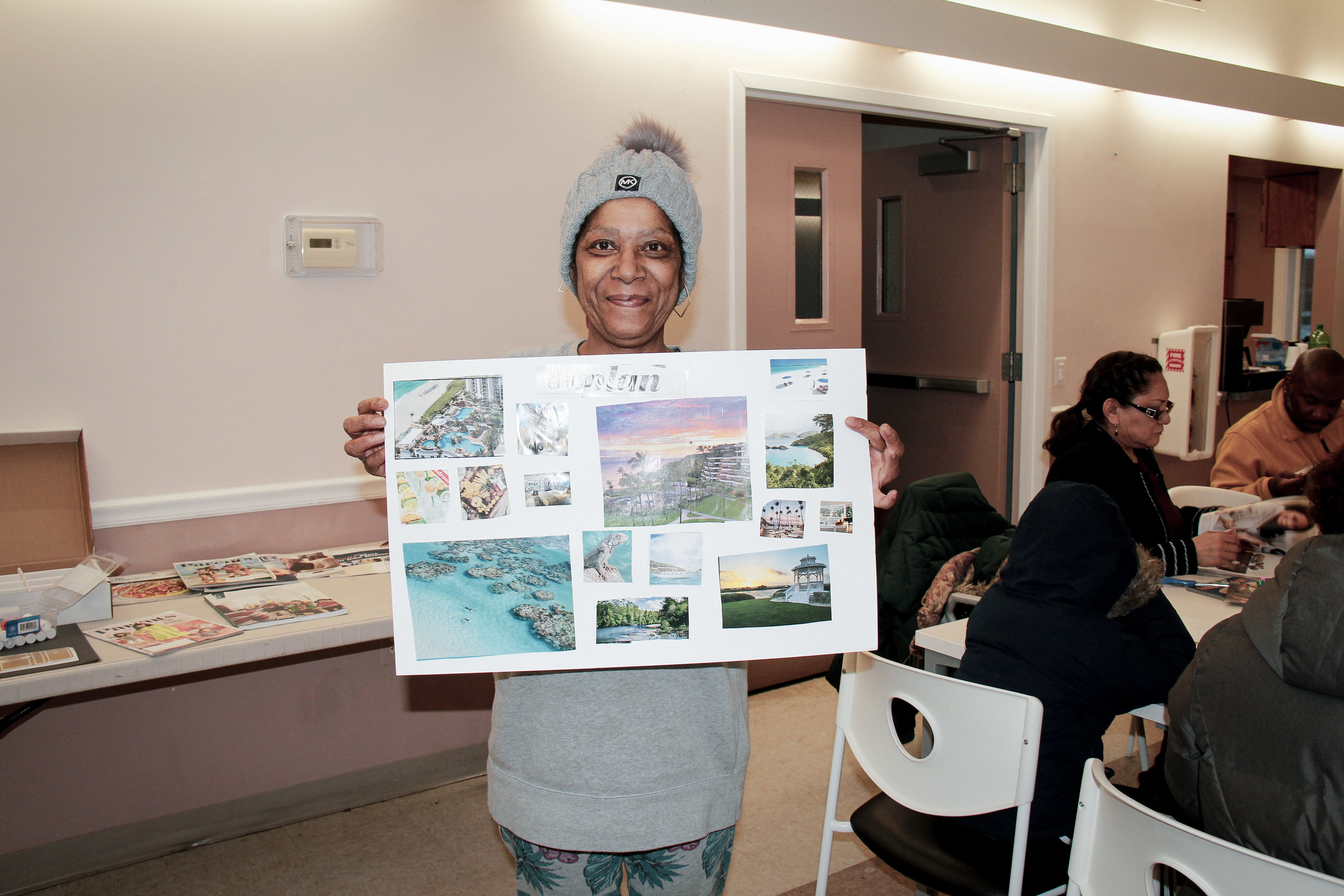 A resident at Bay Meadow Apartments shows off the vision board she made at a community gathering hosted by the Compass FSS program earlier this year