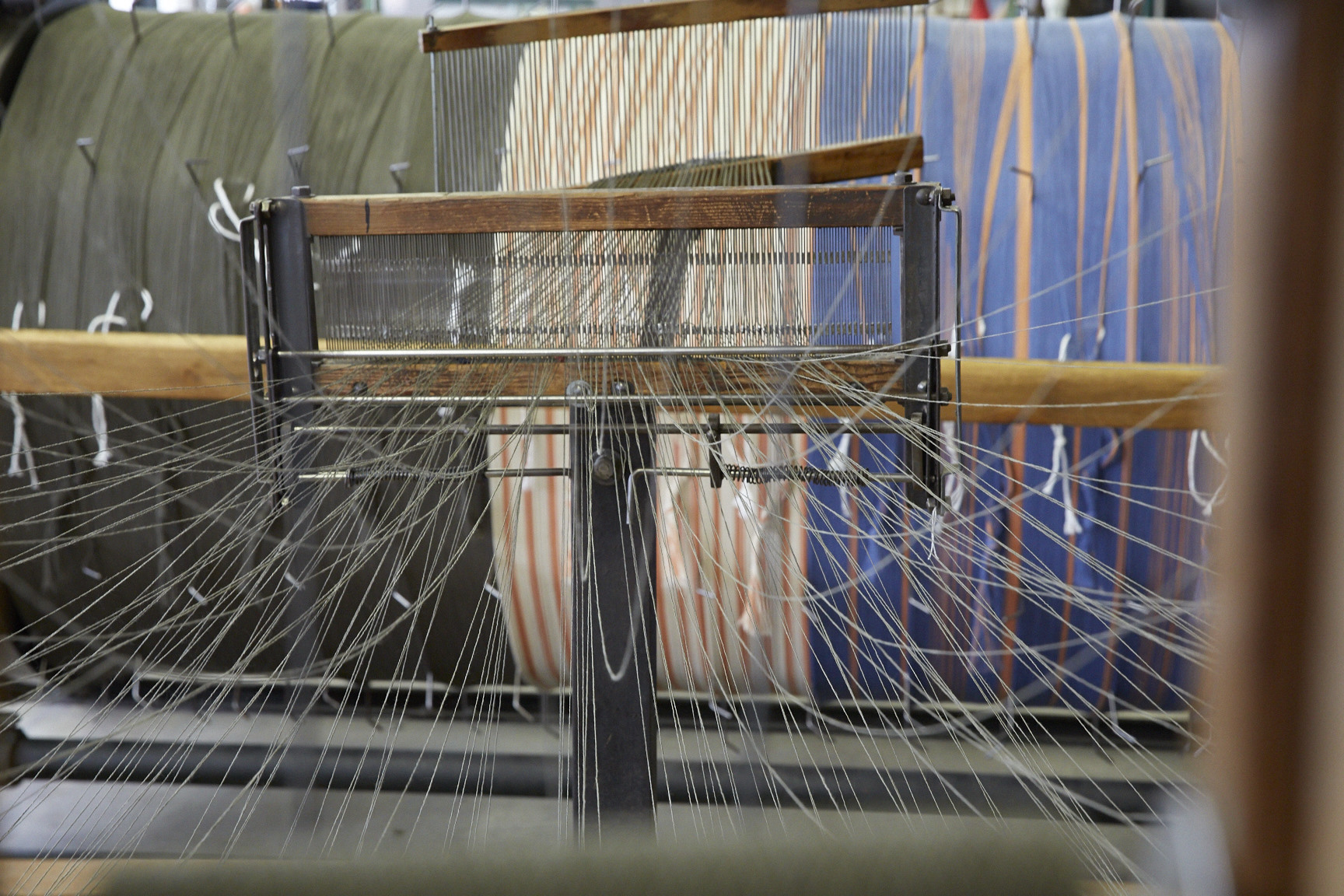 Photo By Jennifer Marx, 2016. 8/2 cotton yarn comes off the cones from a giant spool rack and is wound directly onto a an industrial sized warp drum,which then gets wound onto the back of the Somet loom at The Weaving Mill in Chicago, IL.