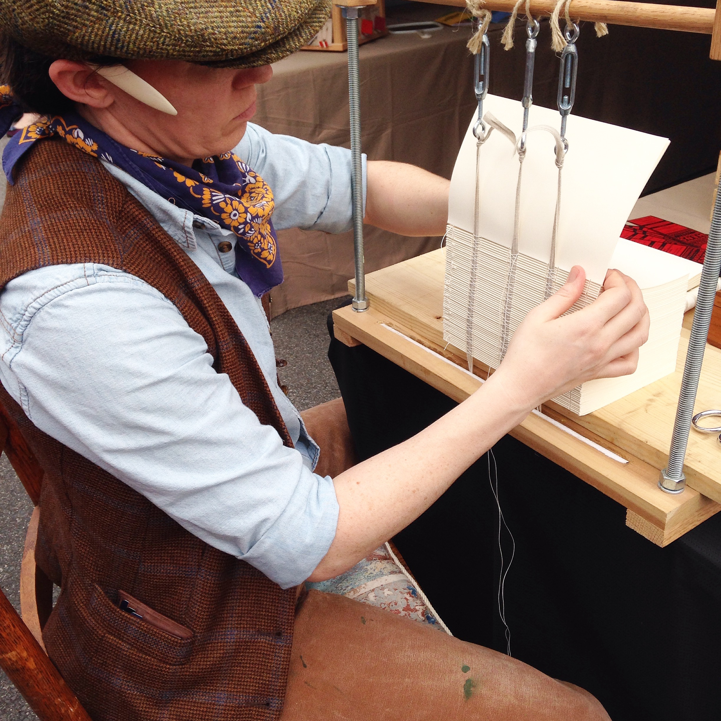 "I do a lot of bookbinding demos at trade shows and festivals towards the end of the year. Last year at ""Dickens of a Christmas"" in historic Franklin, TN I dressed in Victorian garb and sewed books on a frame, a traditional production binding method used at a time when the trade was becoming more mechanized."