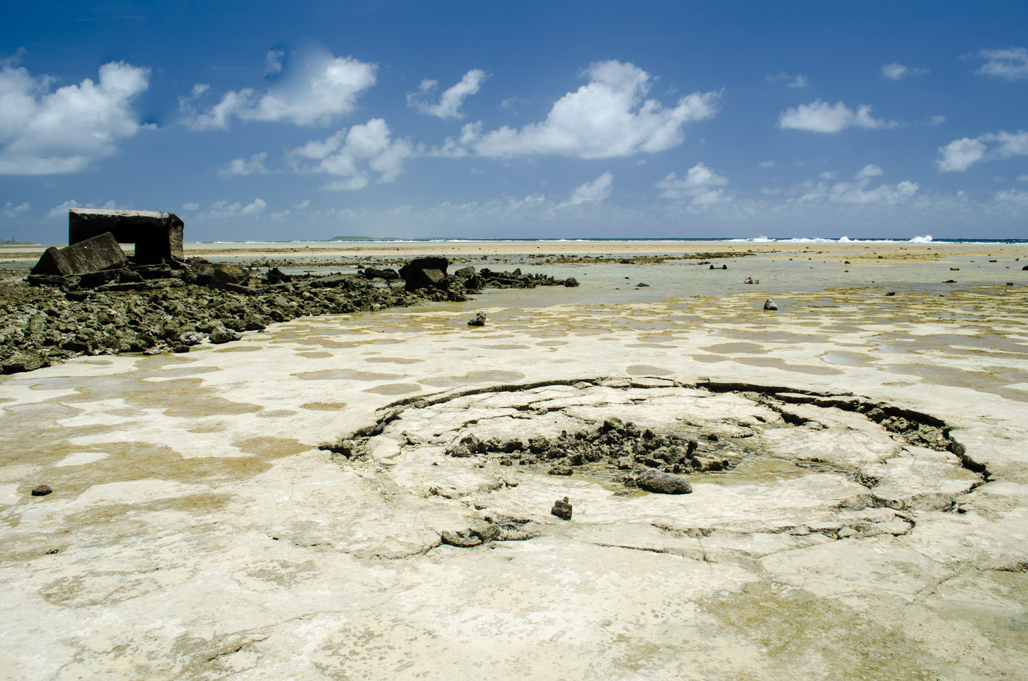 Low tide exposes this crater beside the remains of a bunker
