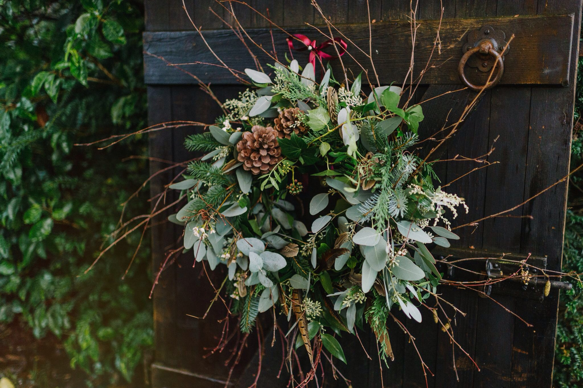 Rustic wreath with mixed foliages, dried Lotus heads, twigs, pine cones, Waxflower and Pheasant feathers.