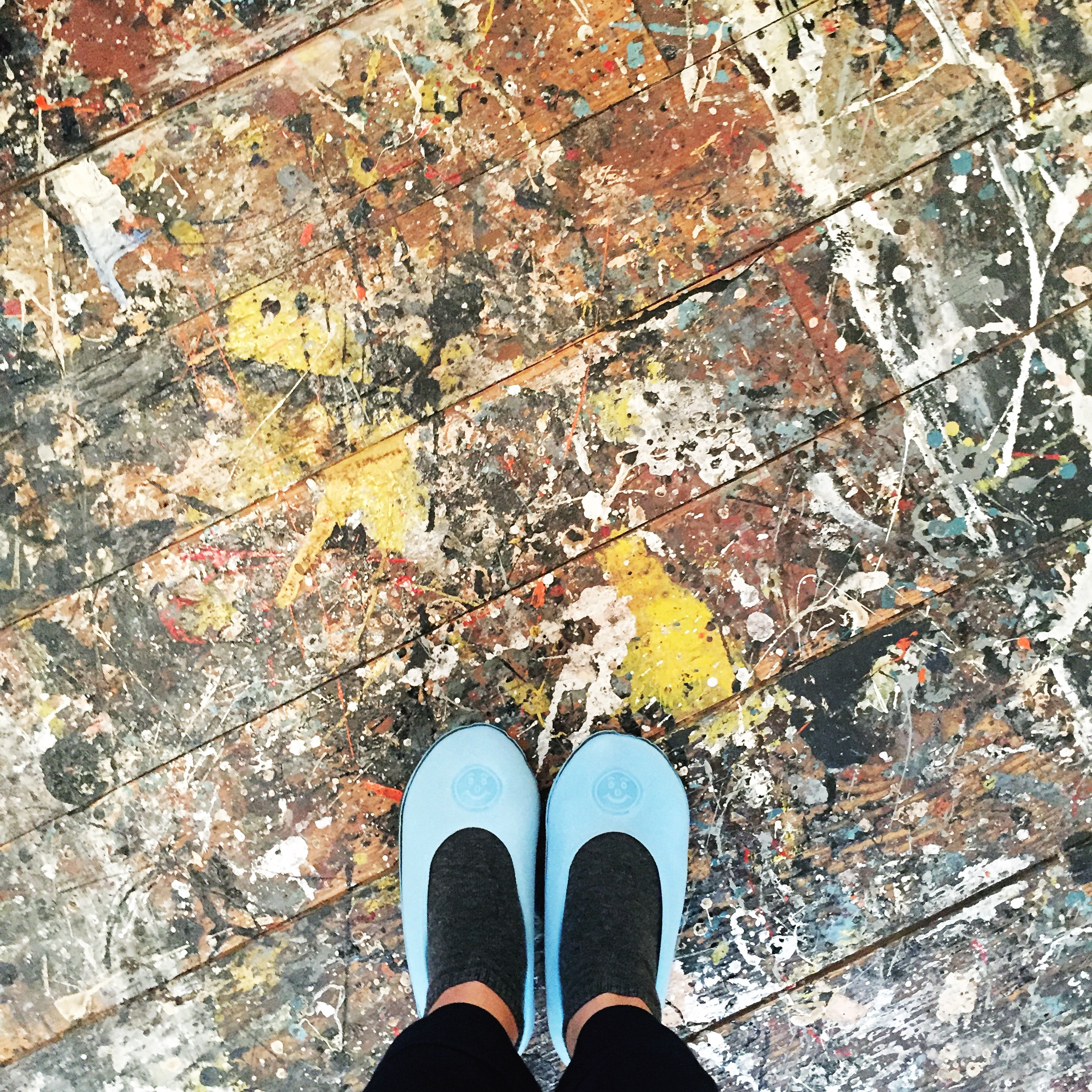 A view of my feet standing on the Pollock splattered floor. The booties are to protect the surface, which by themselves are a work of art.