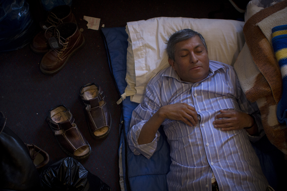 Javier Morán, rests on the floor of the room he shares with a colleague and friends at the Midland Motor Inn.  Morán has been in the United States illegally for over a decade. He originally came to the country with his wife and daughter but they have since gone back to Mexico. Morán speaks to his family regularly and sends them money, but he has not seen them since they left the U.S. eight years ago.
