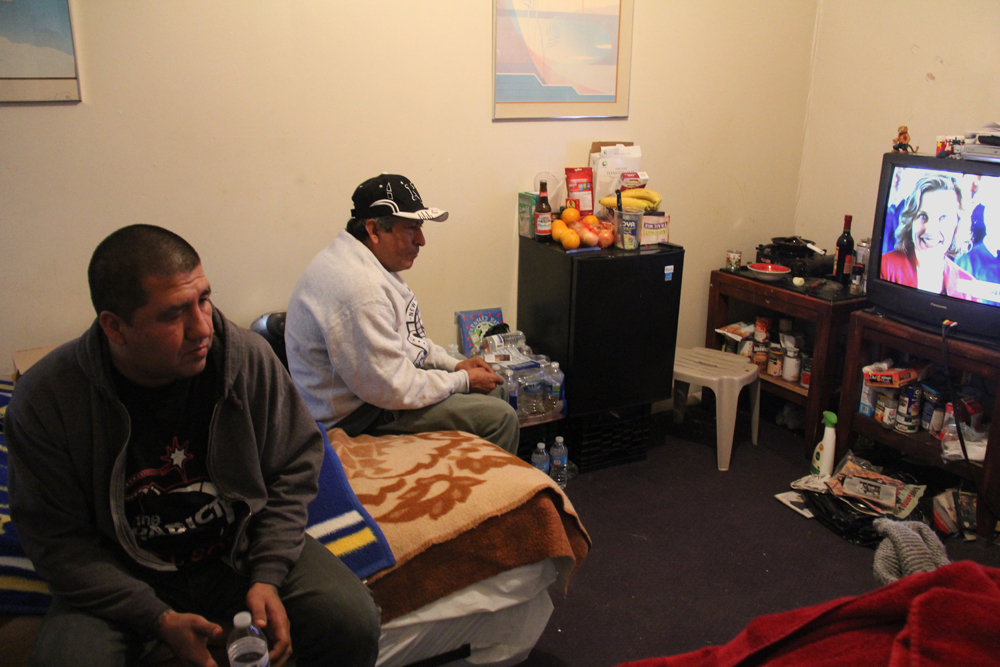 José Parra (left) and Javier Morán sit in their room at the Midland Motor Inn. The two men were given a room free of charge in the motel for the first two months after the storm. They started paying rent as of January, and give their employer $50 a week each, which pays for one room with one bathroom and one queen size bed that they share.