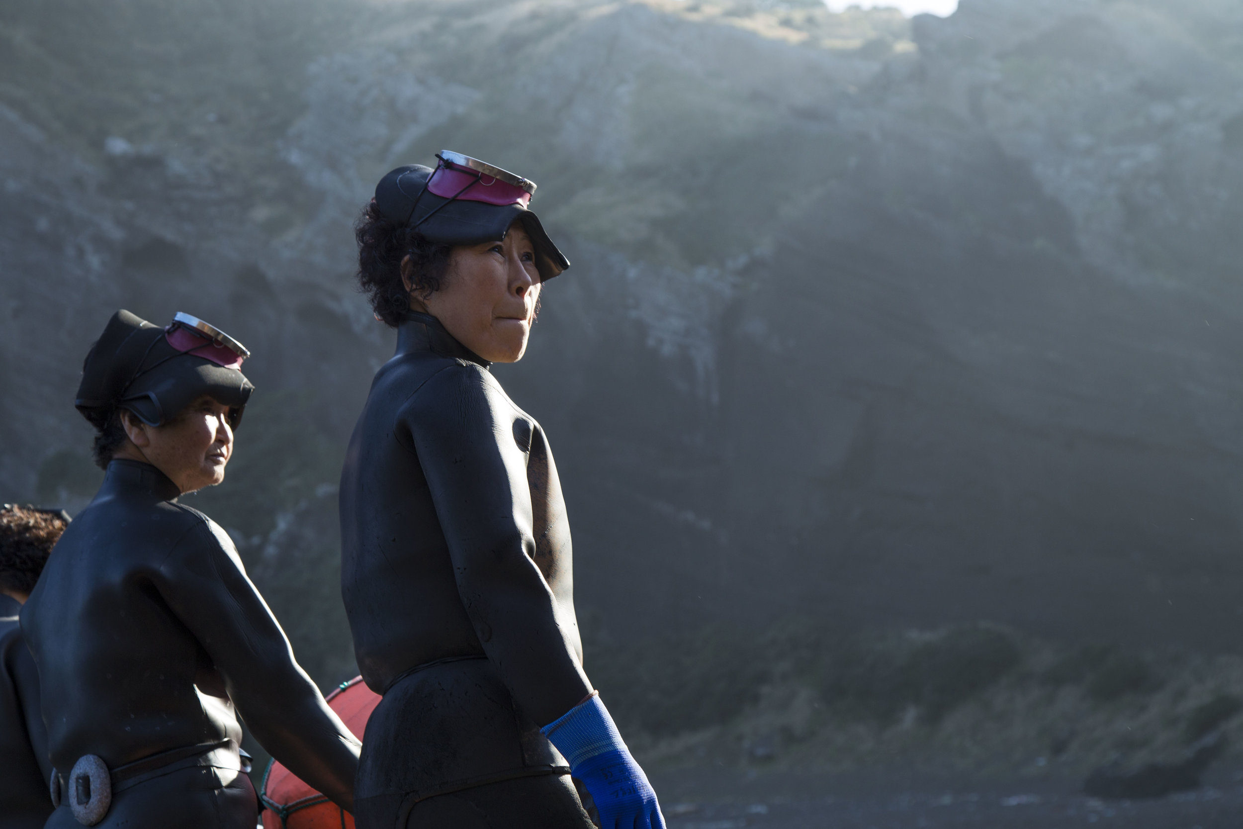 Women divers of Jeju Island, called Haenyeo, prepare for yet another dive into the ocean to collect shellfish from the rocks and seafloor. Using a led weight, they sink deep enough to collect the fish, then pull themselves up along a cord attached to a flotation device above water. Most haenyeo are now over the age of 50, as industrialization and increasing work and educational opportunities for women draw them to other professions. These women represent what may be the last generation of haenyeo.