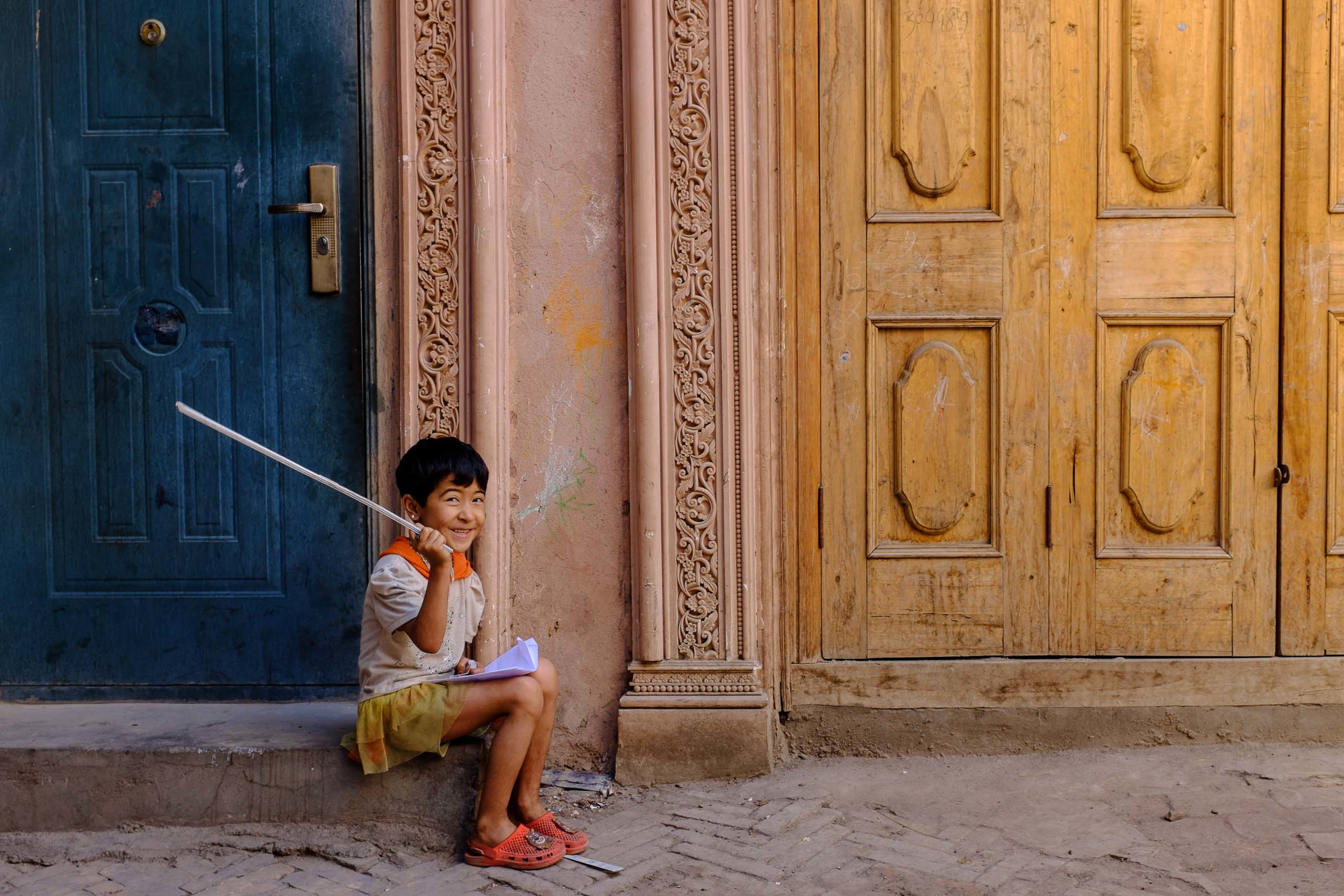 A young girl smiling on a stoop in one of the wandering alleyways of Kashgar's old town