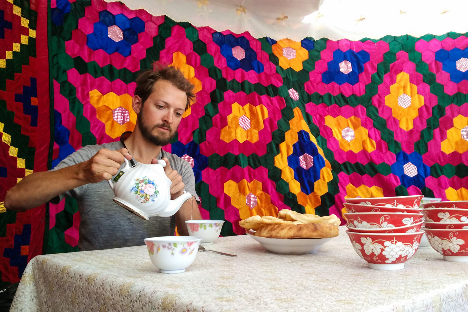 Pouring some tea in a colorful yurt