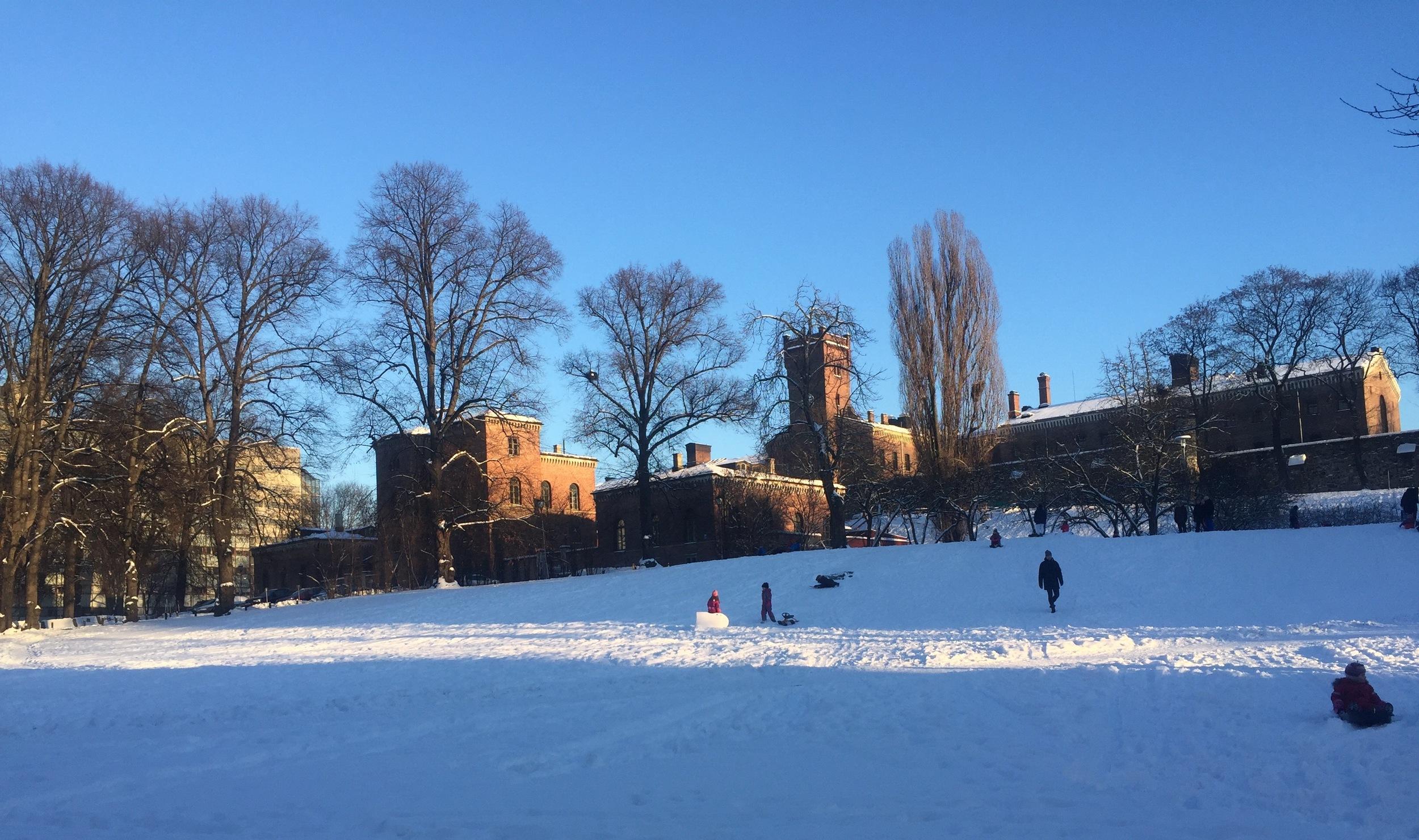 Botsfengselet i bydelen Grønland i Oslo, badet i sol. Foran ligger den snødekte akebakken, som er en yndet ake- og lekeplass for barn.