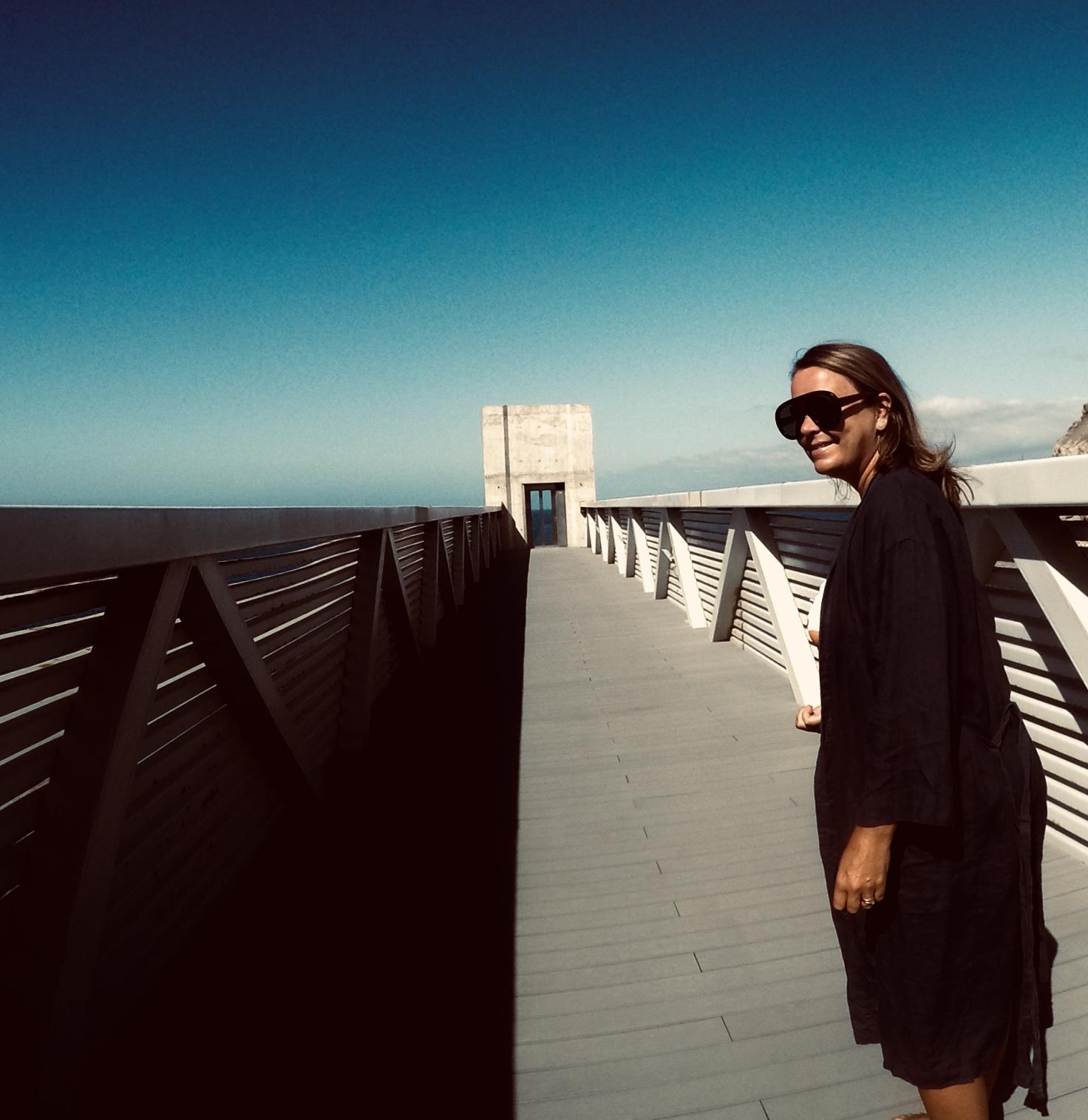 -  Det er bra du har dykkermaske på, for nå skal du bade , kommenterer kjæreste-mannen min. Han er ironisk til solbrillene mine og synes ikke de er fine. Jeg derimot synes de er ultra-lekre! Jeg på broa over til heisen, som tar oss ned til stranda. FOTO: Pelle Knudsen.