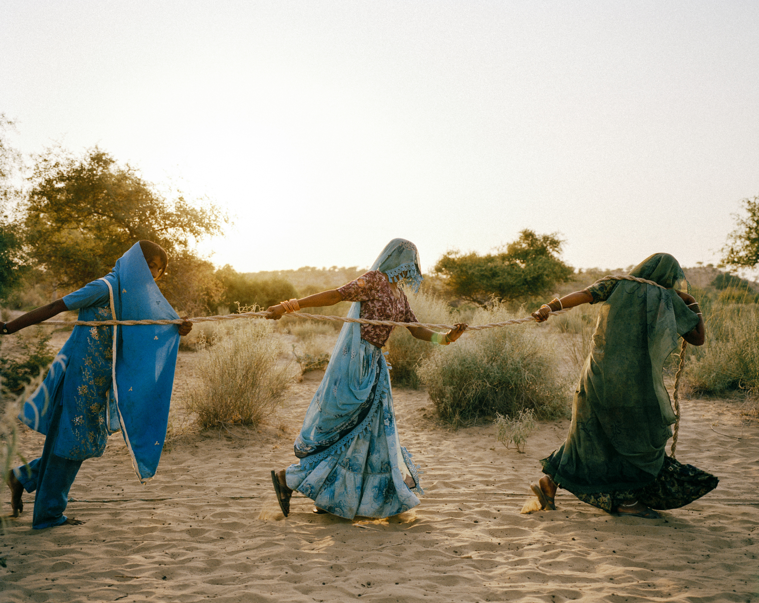 "Women pull water from a well, Tharpakar, Pakistan, 2013.   In the Thar desert, temperatures hover at 48-50°C on summer days. With an extremely low water table and continuing drought, sometimes water must be hauled from a depth of 150-200 feet. ""Women fall unconscious on their way to these dug wells,"" said Marvi Bheel, 45, a resident of Bewatoo, Tharparkar. The unending pursuit for water is a heavy demand on women worldwide. From the water-scarce regions in southern Ethiopia to the desert wells of Pakistan, it is women who are primarily responsible for gathering water. Credit: WaterAid/ Mustafah Abdulaziz"
