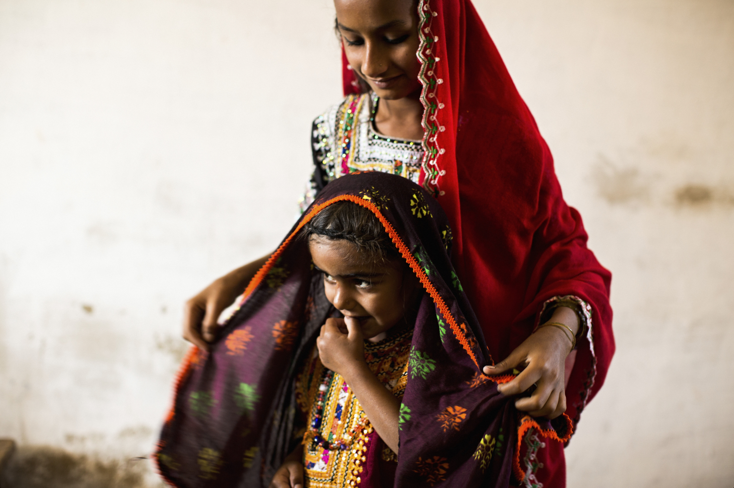 """An older girl fixes her younger classmate's headscarf in Haji Saleh Jat. Residents of the area are famed for their skilled embroidery work. """"The children are so clean and beautiful now,"""" says head teacher Abdul Hakeem. """"That has been a positive change; there is a healthier environment around the school."""""""