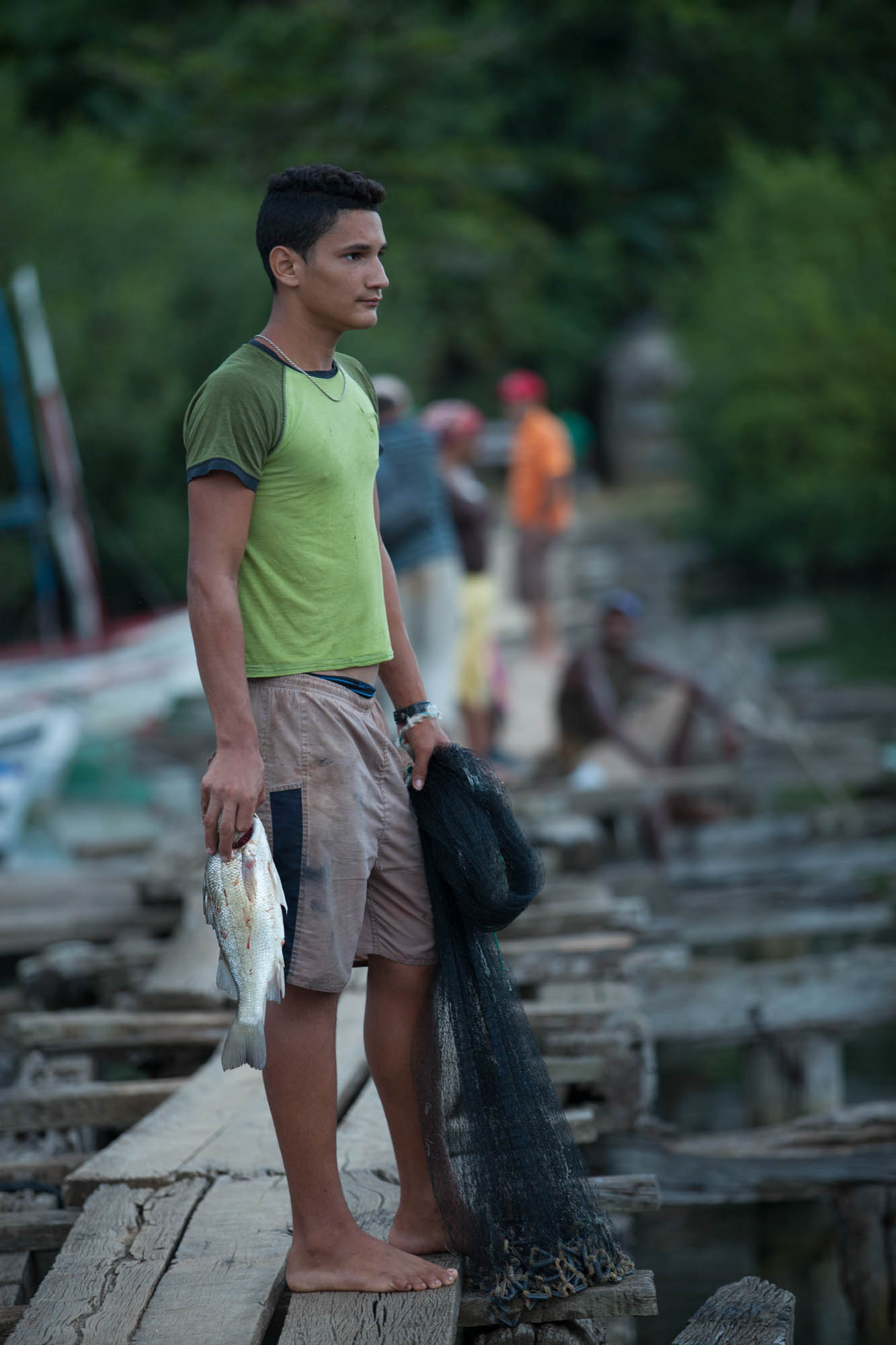 YOUNG FISHERMAN  A young fisherman perched along the floating docks outside Baracoa.
