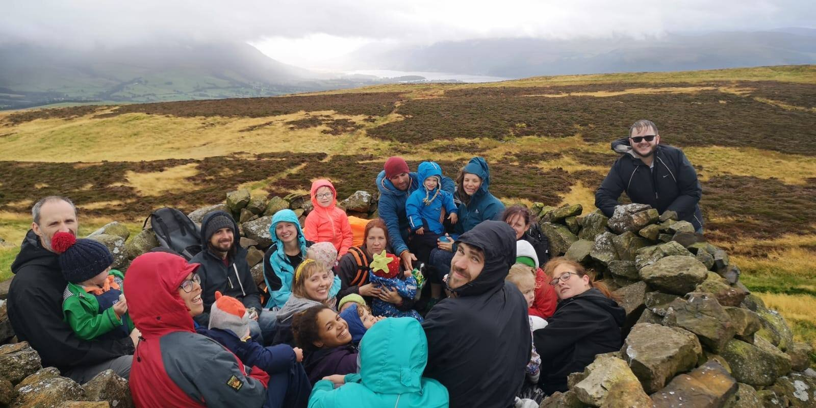 Group of adults and children on the top of Binsey Fell
