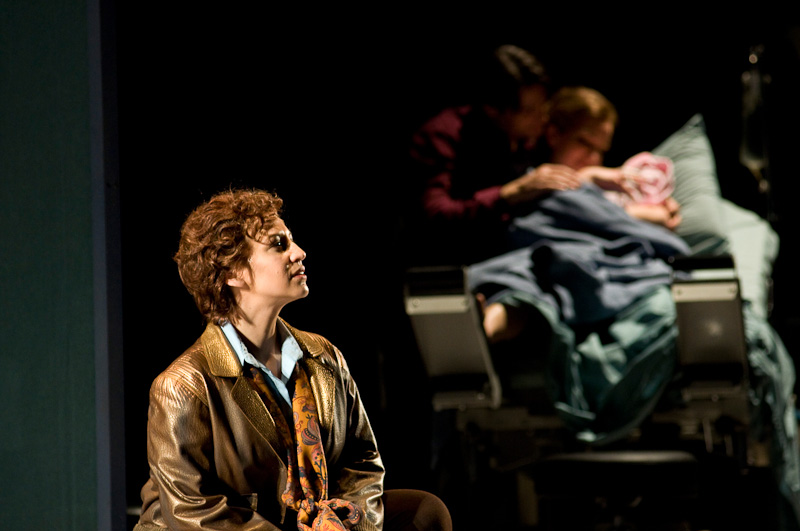 """Amelia Earhart, """"the Flier,"""" (Jennifer Zetlan) surveys her landing site as Paul (Nathan Gunn) and Amelia (Kate Lindsey) cradle their newborn infant in the final moments of the opera. Seattle Opera photo by Rozarii Lynch."""