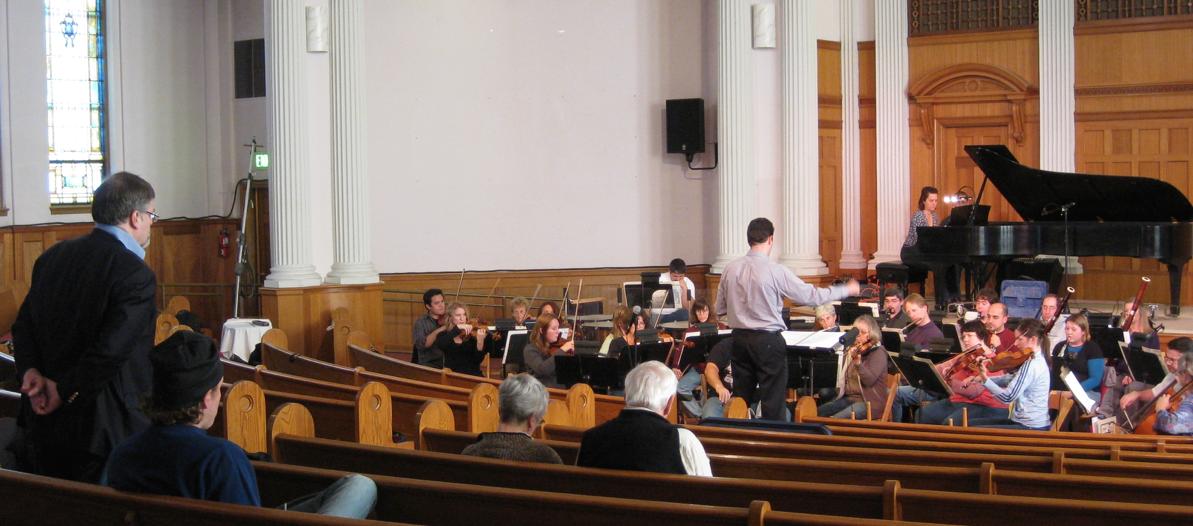 Hagen looks on as Lawrence Golan rehearses the Yakima Symphony, Tanya Stambuk soloist, in the Piano Concerto.