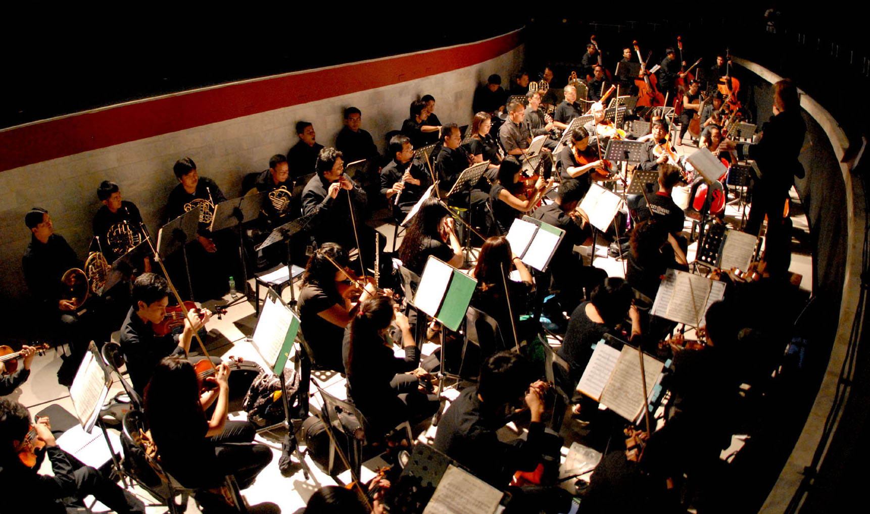 Most orchestras actually play mainly beneath the stage. Here is a pit orchestra arrayed in front of the proscenium.