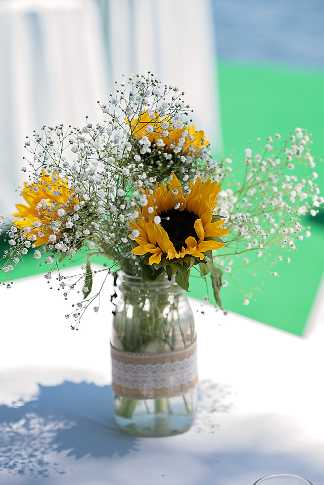 Beautiful sunflowers & baby's breath in mason jars wrapped in burlap were the focal point of the guest's tables.