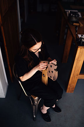 Megan saddle stitching a leather bag in the Stitch & Shutter Studio