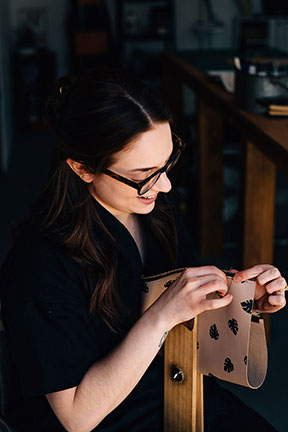 Megan hand stitching a Leather Monstera Print Zip Pouch in the Stitch & Shutter Studio