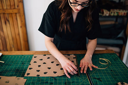 Megan placing a zipper on a leather bag in the Stitch & Shutter Studio