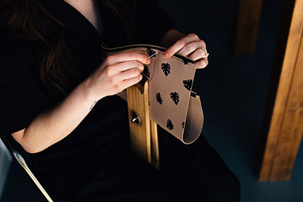 Megan hand stitching a leather bag in the Stitch & Shutter Studio