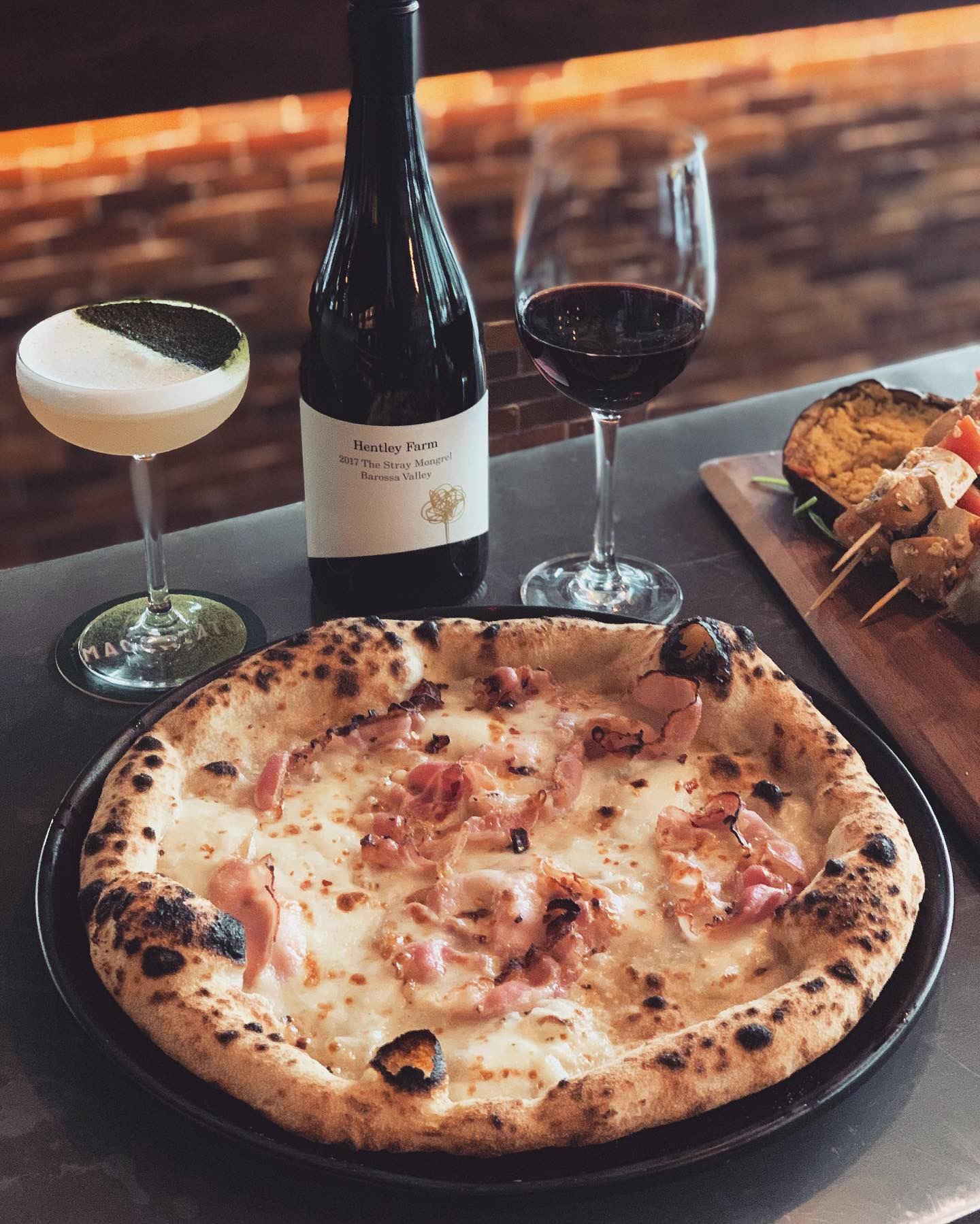31 July-6 August - TGIF!.Pizza time here at Macchiato.This week's special is a pumpkin base pizza with double smoked, leg ham and smoked scamorza cheese. 🤤 .Bring on the Smokey pizza! Recommended with a special wine on the menu, Hentley Farm 'Stray Mongrel' GSZ (Grenache, Shiraz, Zinfandel) from Barossa.