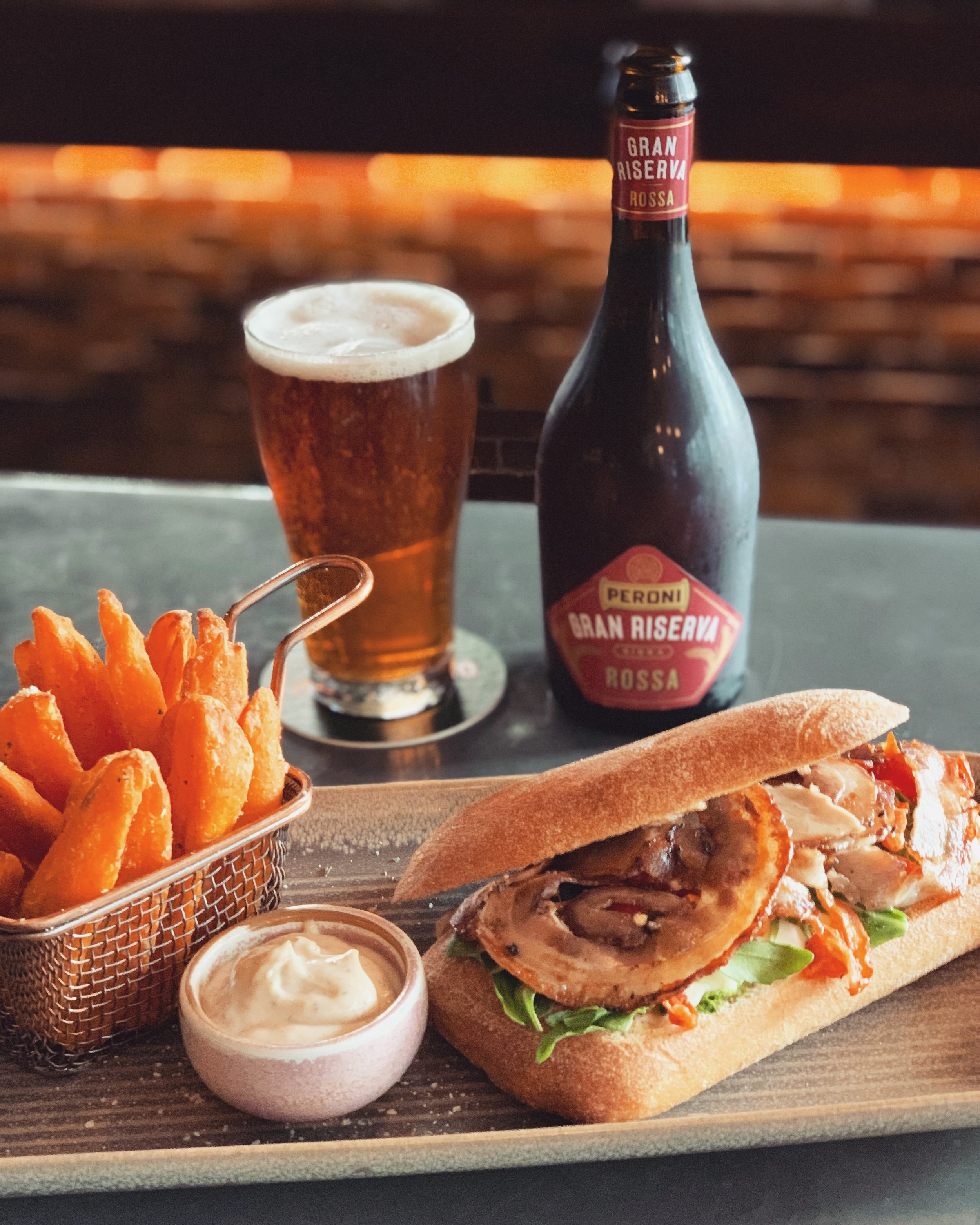 14-20 August - If you're looking for the ultimate lunch fix, then look no further! Delicious slow roasted, thinly sliced porchetta, taleggio cheese and semi dried tomato on a stone baked white ciabatta, with a side of sweet potato fries and truffle aioli..We have NO DOUBT this lunch roll will make your day a little better! Lunch only!.Perfectly quenched by a 500ml Peroni Gran Riserva Rossa 👌🏻🍺