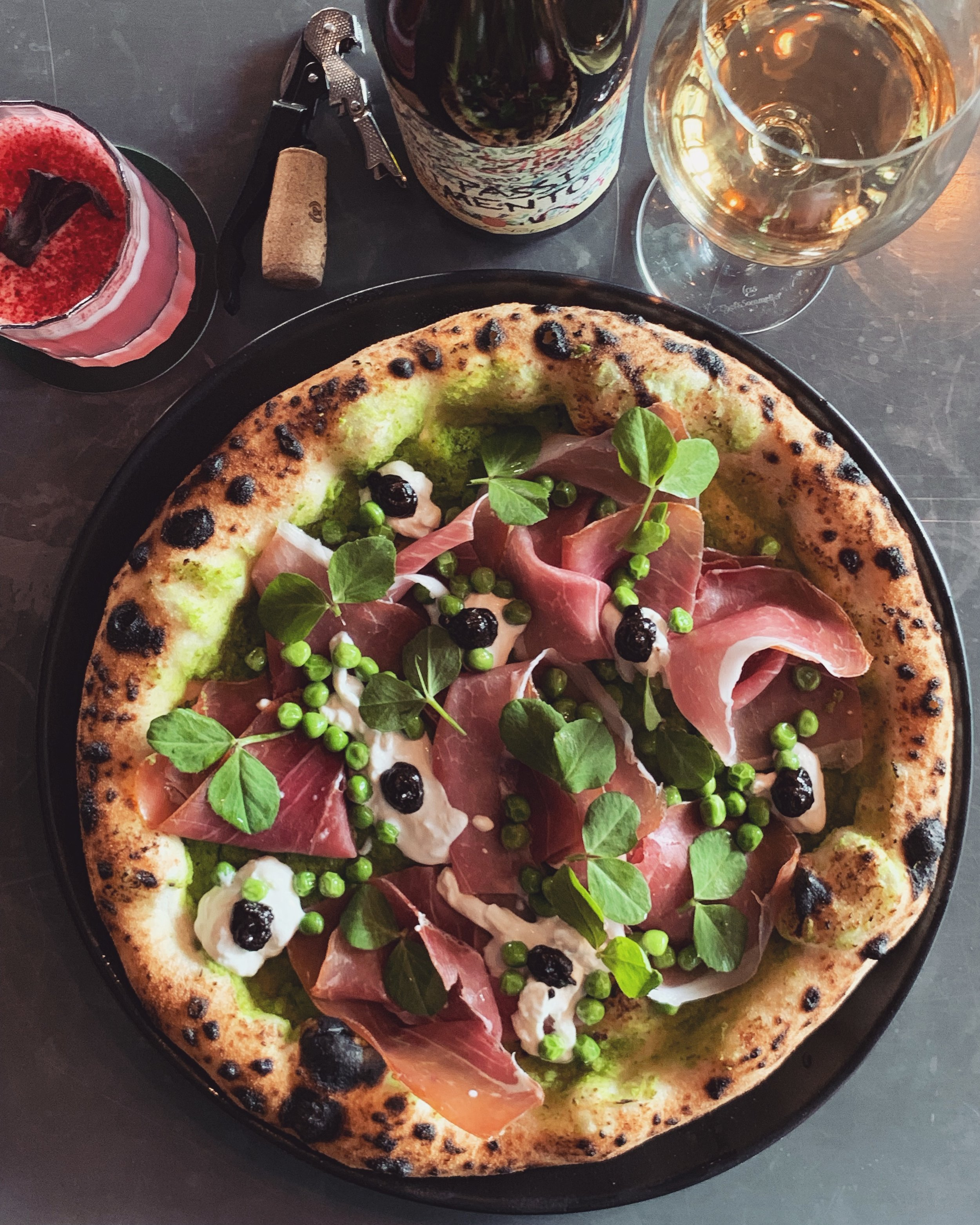 14-20 August - Who said pizza has to be red? 🍕 We tried red, white and green (pesto) but this week we used smashed green peas to create a delicious and nutritious pizza sauce..// Prosciutto di Parma, smashed green peas, stracciatella cheese, confit black garlic. //.Happy Thursday everyone!