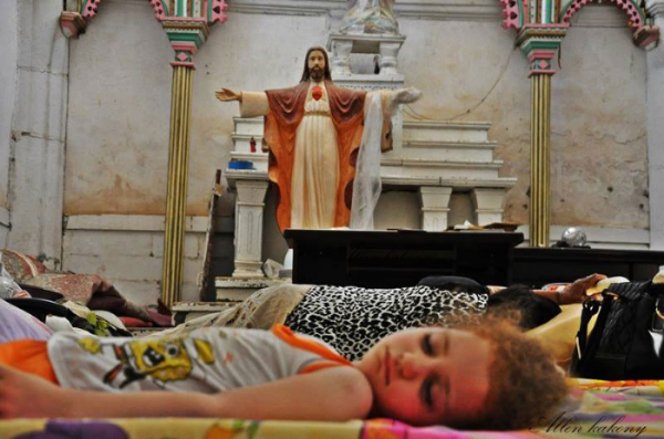 An internally displaced child sleeps on the floor of St. Joseph's Church in Arbil, Iraq.  (Photo courtesy of Allen Kakony/A Demand For Action)