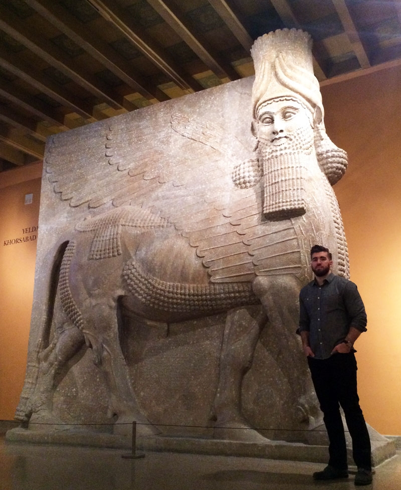 "Paul Khio stands in front of an Assyrian winged bull, also called a Lamassu, at the Oriental Institute Museum's Assyrian gallery in Chicago. The figure behind him is similar to what radical Islamic militants destroyed in Iraq. ""History is the yearning of children for the knowledge bestowed upon them by their forefathers,"" he said.  (Photo by Ramsen Shamon)"