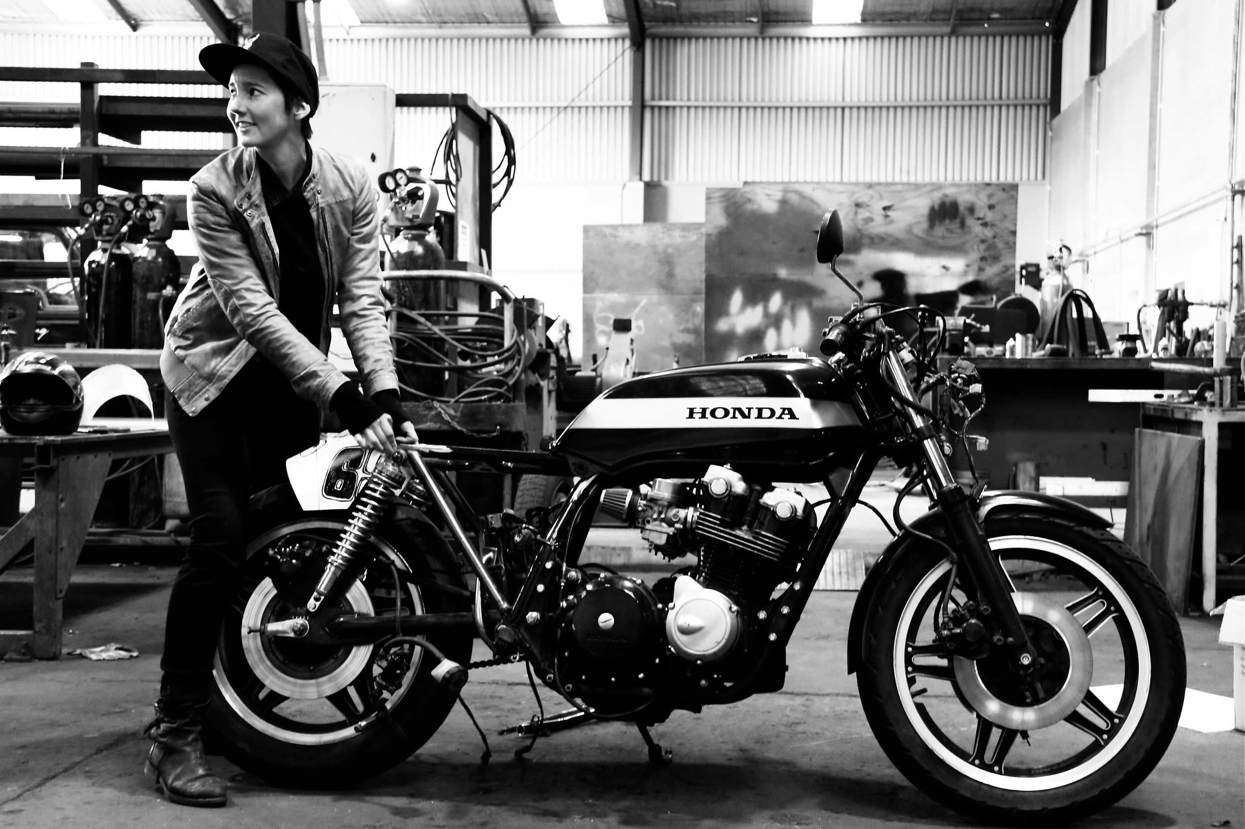 """Rosie is currently in the process of following her dreams with insuppressible thirst. She rides a 1977 Honda CB550four Super Sport and is building a 1982 Honda CB750four with the help of her engineer husband Dan. She's called """"Bogan Audrey,"""" and it is a rat racer style café racer. Rosie's inspiration for this dream machine: Audrey Hepburn in a little black dress. Rosie grew up around bikes and started out on dirt/motocross bikes. """"My first race bike was at Yamaha pw50 at age four, I progressed through to come third in NZ for junior women and then had a big accident on my Honda CR125 (two-stroke) where I broke both my wrists at the same time."""" Rosie's still got plans for the track and her big dream is to build her house around her workshop. She's working on her welding skills like a mad women and has all kinds of ideas for builds. He favorite kind of therapy is working on one of her many projects or going fast. See if you can catch her!"""