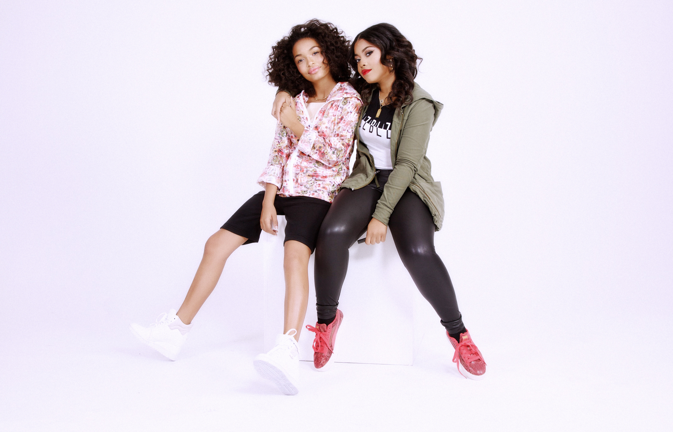 "Yara (left) wearing ""Sunrise in Harlem"" Lipmatic gloss, jacket by Top Shop, shorts by HLZBLZ and sneakers by Puma. Destiny wearing ""Rose out of Concrete"" Lipmatic gloss, jacket by James Perse, top by HLZBLZ, and sneakers by Puma."
