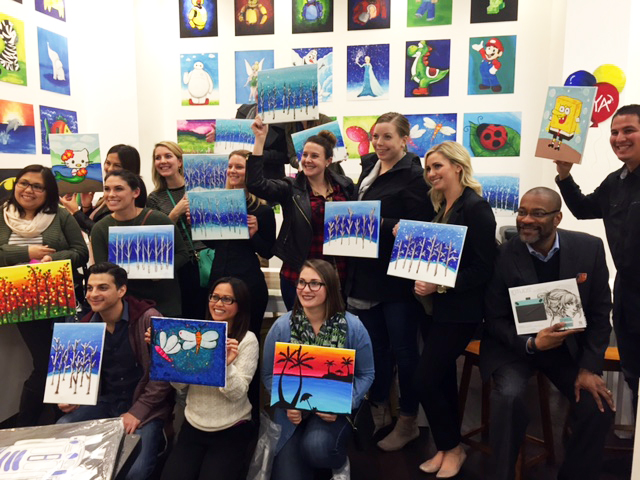 Group of adults holding their paintings.