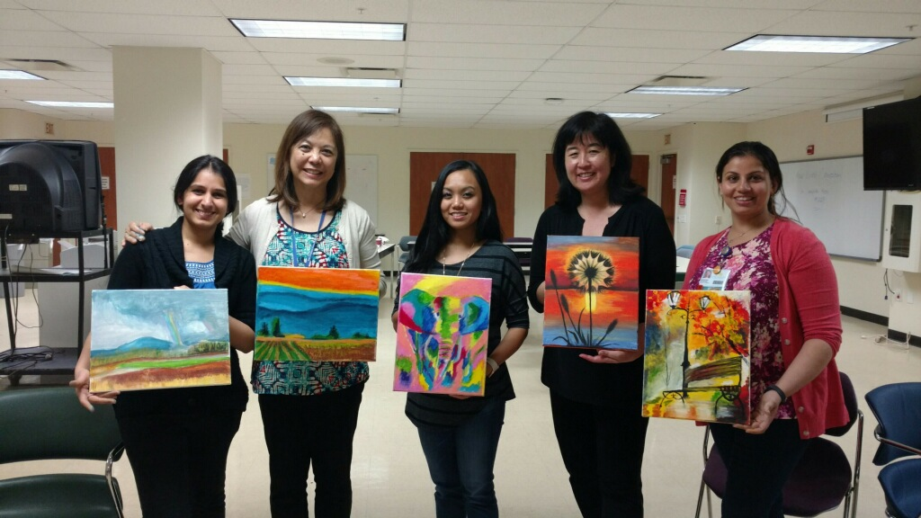 Image of a group of women holding their paintings.