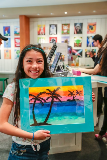 image of student holding her art piece of a sunset
