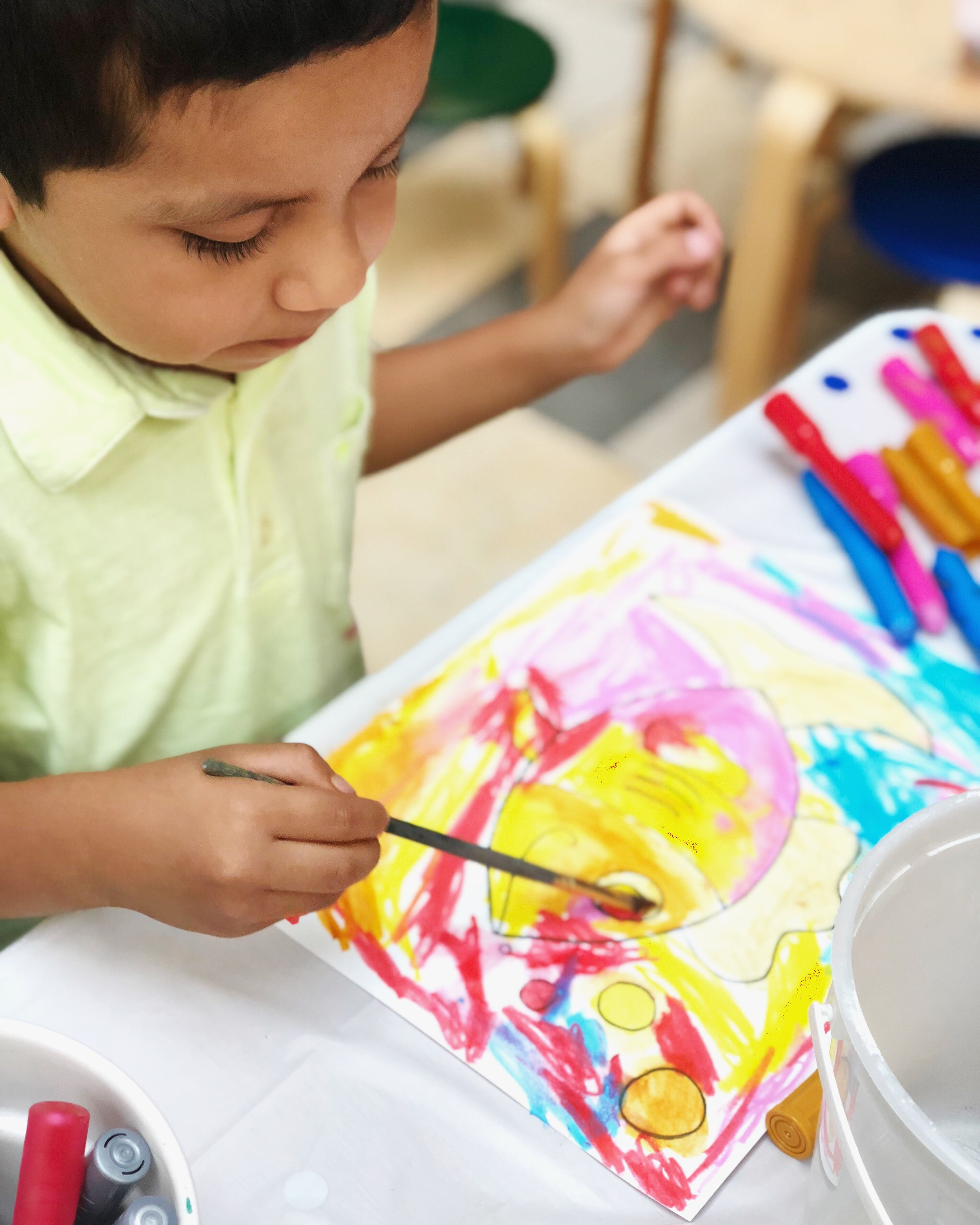 image of a boy painting a colorful fish