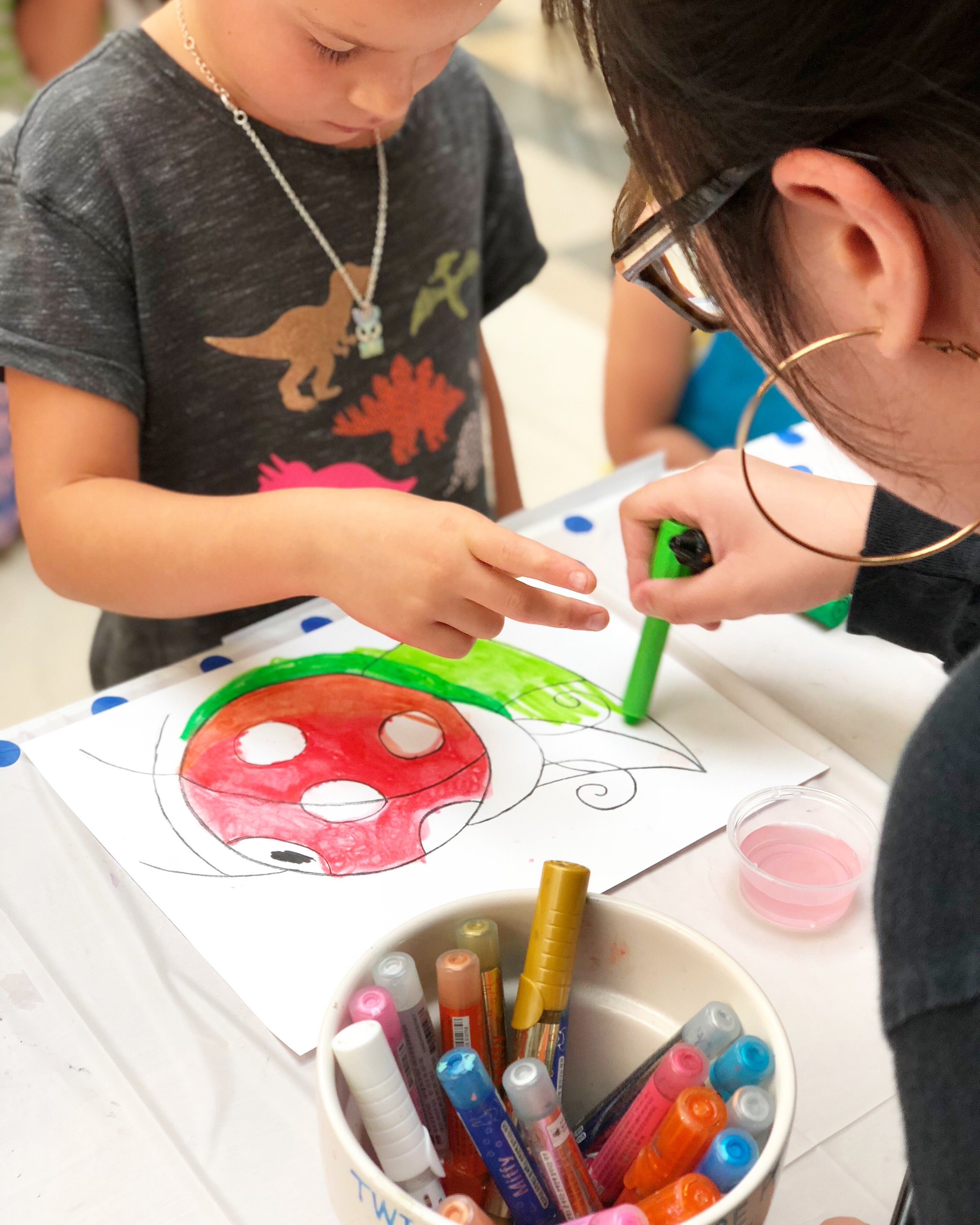 image of young girl painting a ladybug