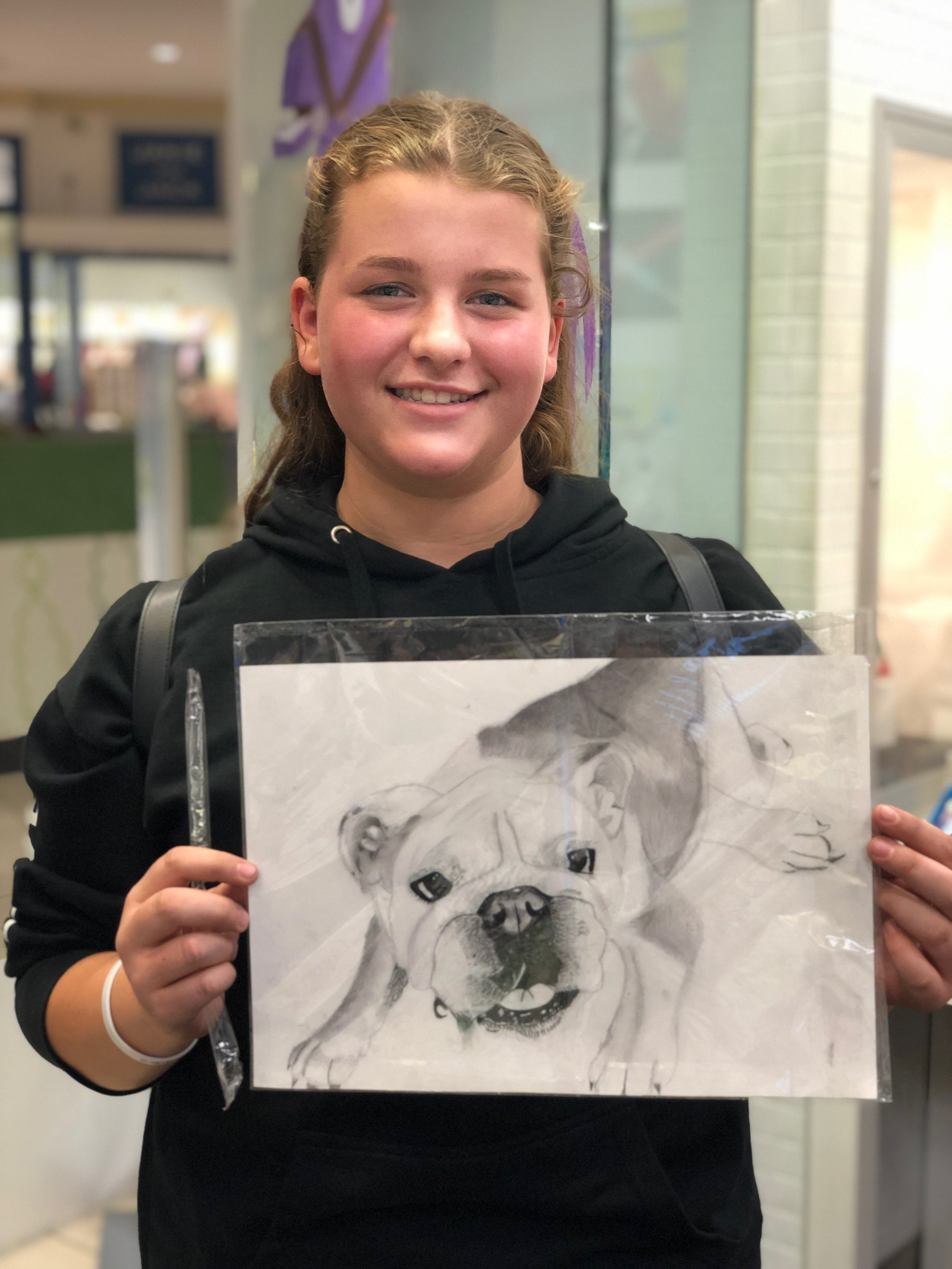 Student holding their drawing.