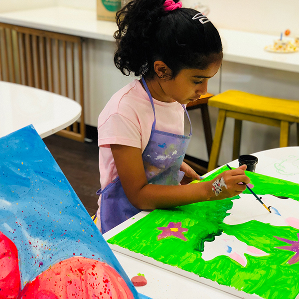 Student painting a canvas.