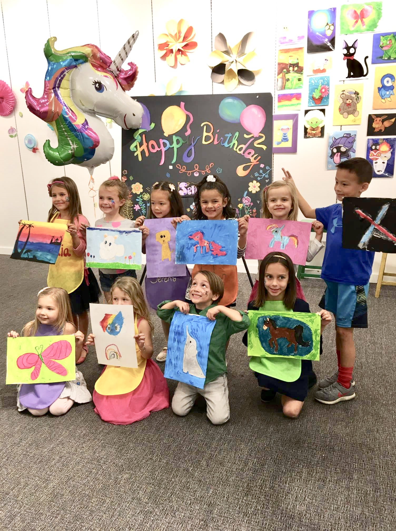 Kids holding their paintings
