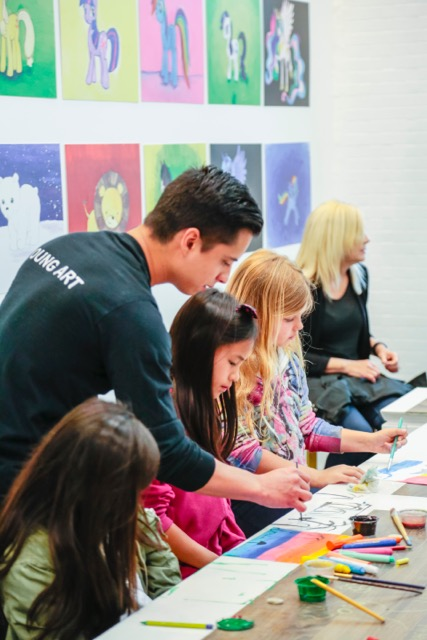 teacher assisting students with their artwork.jpeg