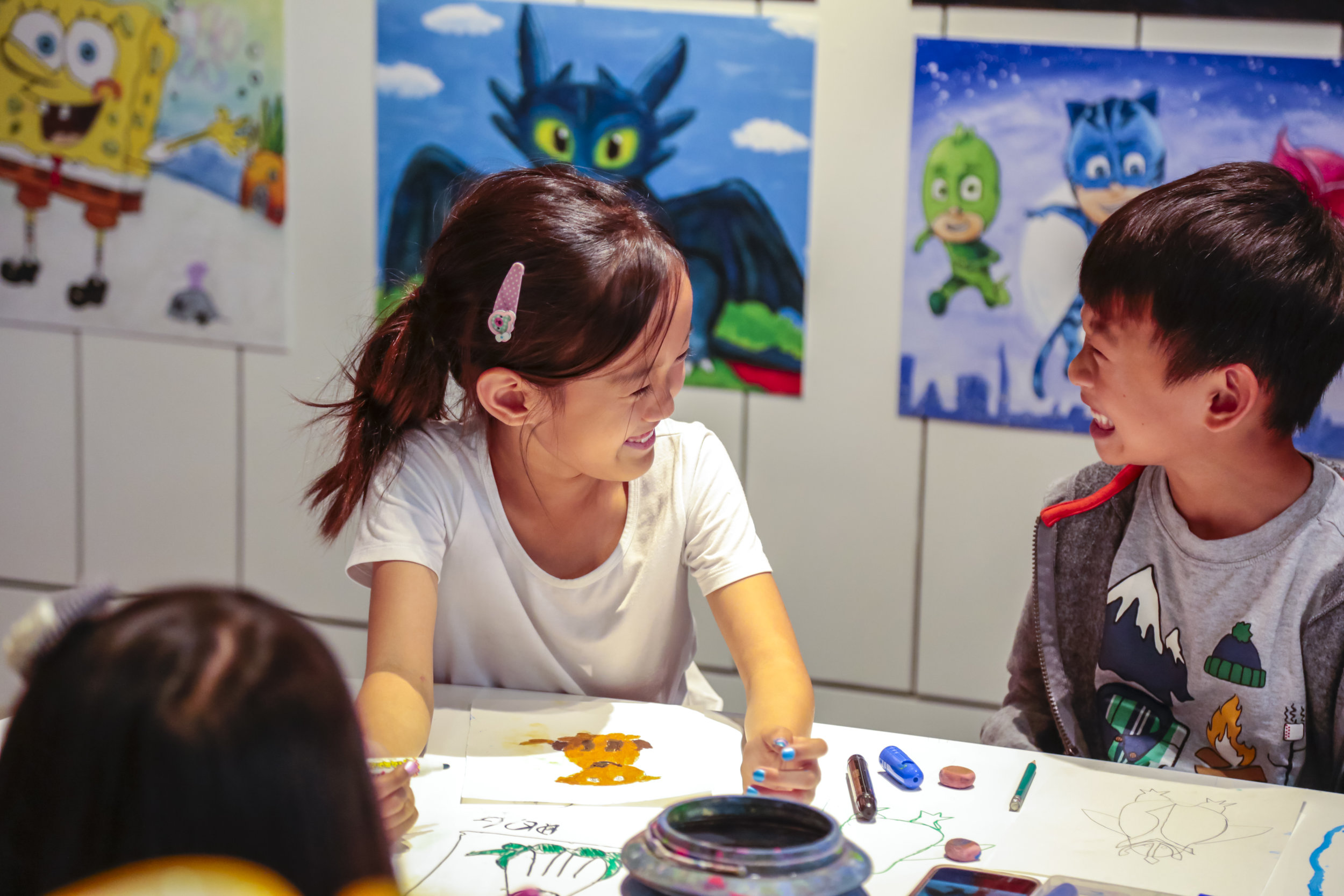 kids laughing while doing an art lesson.JPG