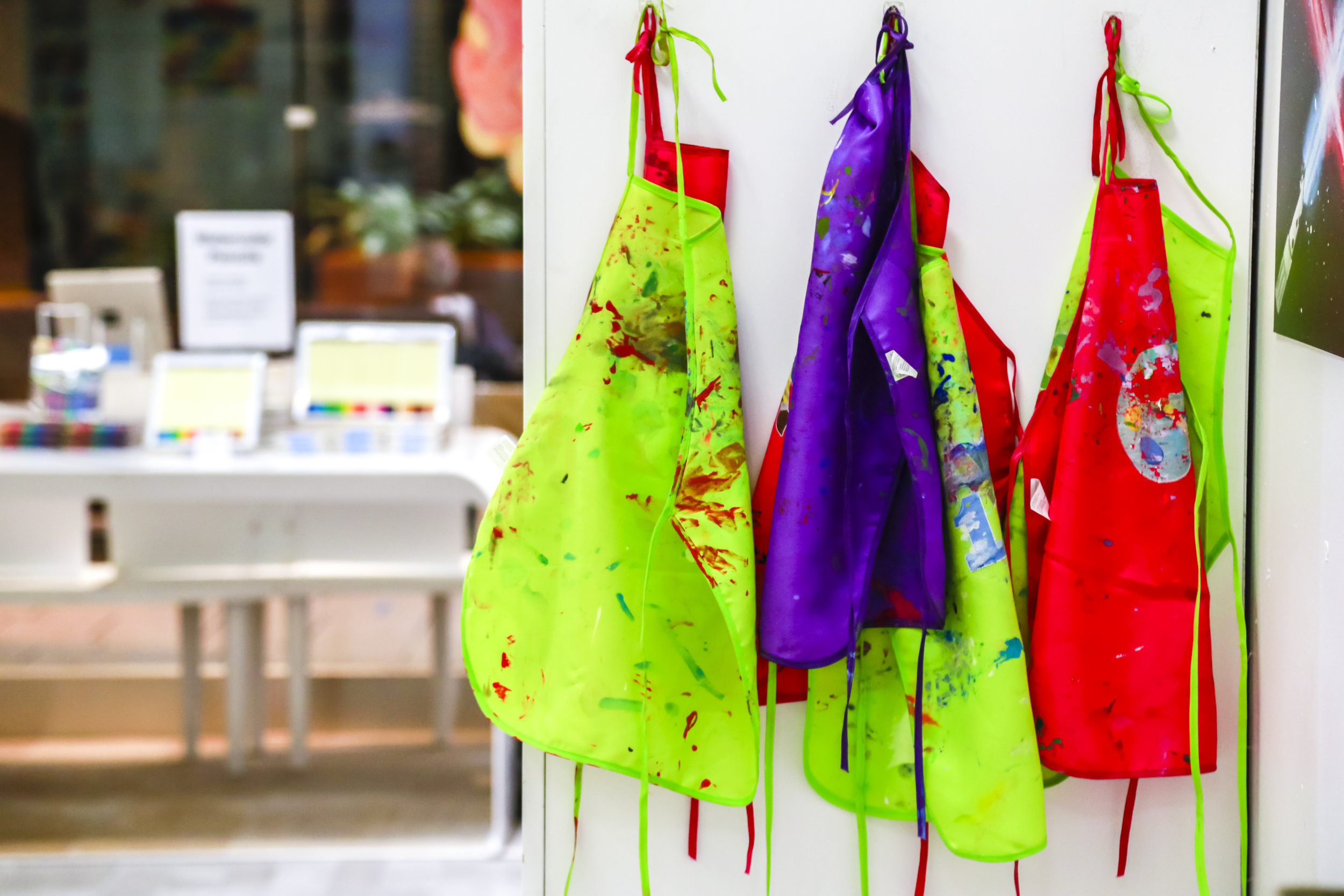 aprons with paint on them hanging up.JPG
