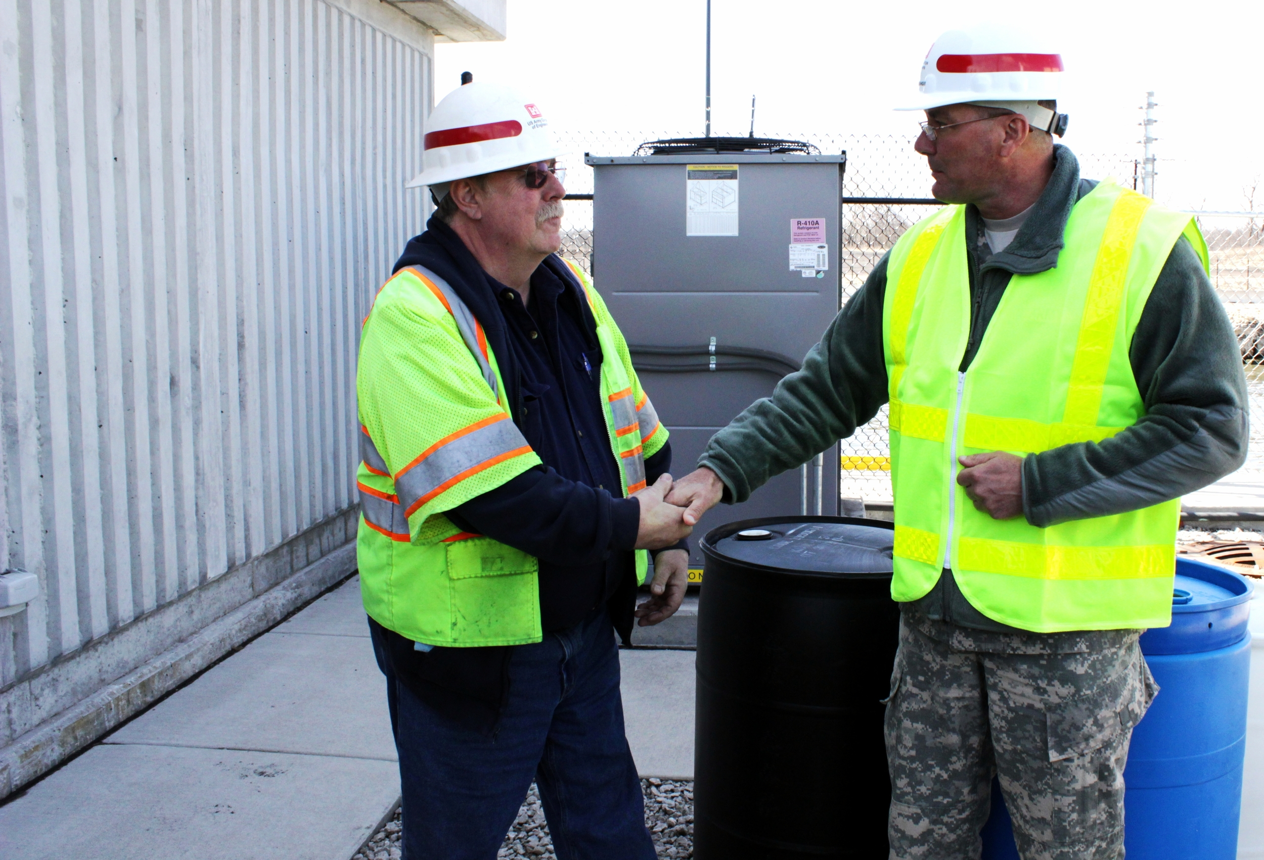 """U.S. Army Photo """" Electric Barrier Facility Manager John McGowan Receives Coin from Command Sgt. Maj. Groninger """" by  Sarah Gross /Released is licensed under  CC BY 2.0 ."""