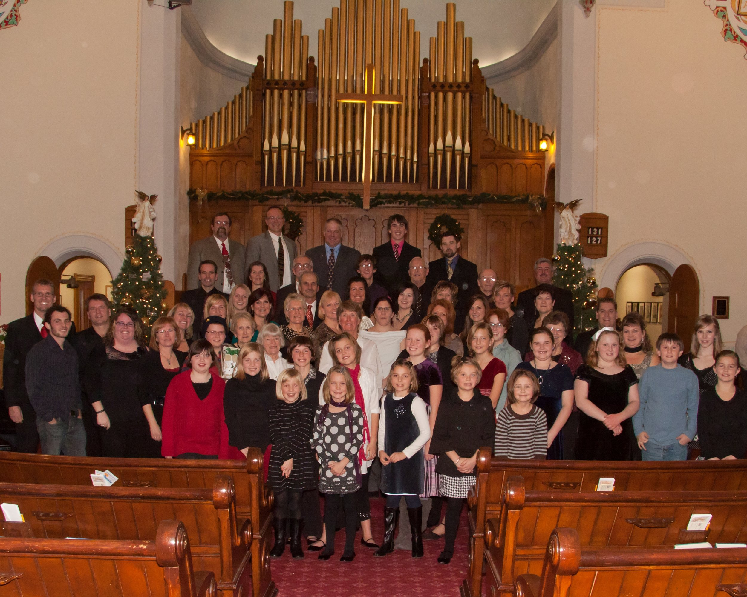 "2010 ""Music of Christmas"" Concert Back row: (Left to Right)  John Chapman, Allan Rothwell, Doug Johnston, Donald Skinner, Stewart Skinner  6th row:  Larry Skinner, Janet McDonald (keyboard) Don Harrison, Lee Mayes, Jim Henderson, Charlie Corry, Brian Hamilton  5th row:  Lauren Johns, Paul Karges, Lynn Kerr, Lisa Schaefer, Kelly Henderson, Jill Reading, Jean Jinkinson, Tyler Schaefer  4th row:  Chris McIntosh (drums), Brian McMurren (bass guitar), Agnes Henderson (piano), Karli Purcell, Kim Henderson, Lois Aitchison, Laura Tryssenaar, Jessica Drummond, Michelle Hemingway, Alicia Lockie, Gloria McCallum, Ethel Corry, Lee Anne Andriessen, Kathleen Skinner  3rd row:  Patrick Main (guitar), Nicole Kaufman, Nancy Skinner (conductor), Noah Andriessen, Marlene Henderson, Grace Burrough, Marion Bristowe, Heather Dafoe  2nd row:  (Children's Choir) Alexis Johnston, Hayleigh Royce, Ann Rothwell, Marlee Ament, Erica Hemingway, Mallory Coleman, Brooklyn Johnston, Emily MacKay, Ryan Mayes, Claire Calder  Front row:  Emily Royce, Brynn Ament, Chloe Hemingway, Sarah Reading, Kayla Fletcher"